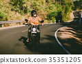 man riding motorbike on a road 35351205