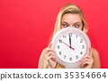 Woman holding clock showing nearly 12 35354664