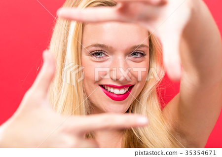 Young woman framing her face with her fingers  35354671