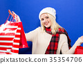 Happy young woman holding shopping bags  35354706