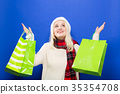 Happy young woman holding shopping bags  35354708