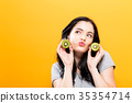 Happy young woman holding kiwis 35354714