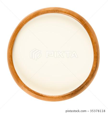 Fresh sweet cream in wooden bowl over white 35378118