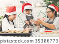 Asian family wear Santa hats preparing the dough 35386773