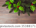 Holly and fir twigs on wood wall 35388171