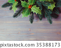 Holly and fir twigs on wood wall 35388173