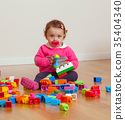 Toddler baby girl playing with rubber building blocks. 35404340