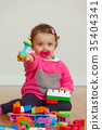 Toddler baby girl playing with rubber building blocks. 35404341