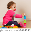 Toddler baby girl playing with rubber building blocks. 35404342