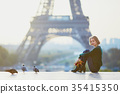 Beautiful young French woman near the Eiffel tower in Paris 35415350