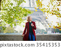 Beautiful young French woman near the Eiffel tower in Paris 35415353