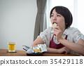 แม่บ้านสาวกำลังกินขนมอยู่ 35429118