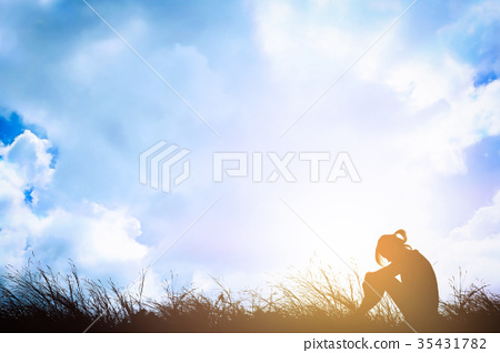 Woman depressed sitting alone on meadow. 35431782
