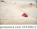 Travel concept. Red model toy car on sand near 35436612