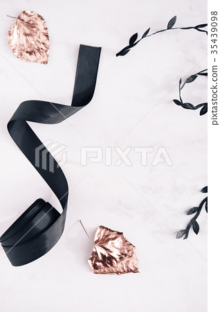 Fall flatlay with black ribbon and gold leaves 35439098