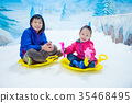 boy and girl riding sleigh on ice in snow land 35468495