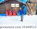 boy holding sleigh standing on ice in snow land 35468515