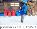 boy holding sleigh standing on ice in snow land 35468516