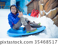 boy riding sleigh on ice in indoor snow land 35468517