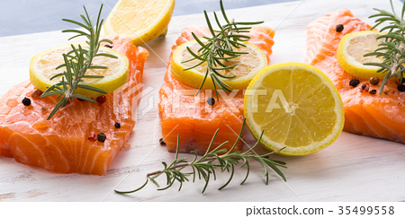 Raw salmon on wooden board with herbs 35499558