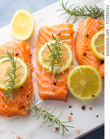 Raw salmon on wooden board with herbs 35499562