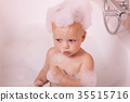 Serious toddler in a bath with foam crown on his 35515716