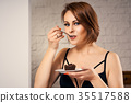 Attractive woman eating chocolate cake on couch 35517588