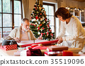 Senior couple in sweaters wrapping Christmas gifts 35519096