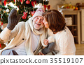 Senior couple in front of Christmas tree enjoying 35519107