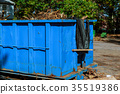 Dumpsters being full with garbage in a city. 35519386