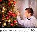 Man dressing Christmas tree. 35520655