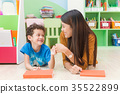 woman teacher teaching kid in kindergarten class. 35522899