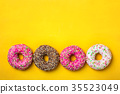 Four donuts in line on yellow background 35523049