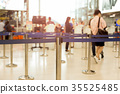 Passengers walking through check-in line 35525485