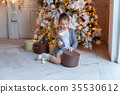 Young girl opens a gift under a Christmas tree 35530612