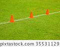 Orange cones on turf football. 35531129