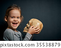 adorable little girl poses with a skull 35538879