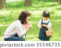 พ่อแม่และเด็กเล่นในสวนสาธารณะ 35546735