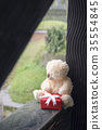 Stuffed toy with a gift on a wooden beam 35554845