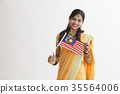 Indian woman in traditional clothing holding flag 35564006