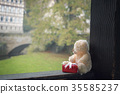 Teddy bear and gift on a wooden beam 35585237