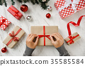 Female hands wrapping a brown present box. 35585584