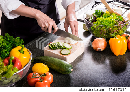 Healthy Woman makes fresh vegetable salad with olive oil, tomato 35617013