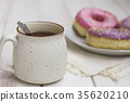 Cup of tea and fresh donuts in white plate 35620210