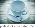 White ceramic cup saucer teaspoon on wooden board 35620751