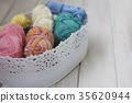 Multicolored yarn in basket on white background 35620944