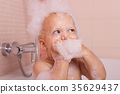 Funny toddler in a foam taking a bath and looking 35629437
