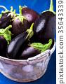 Fresh eggplant in grey basket on blue wooden tabl 35643339