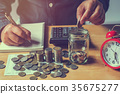 businesswoman saving money with putting coins 35675277