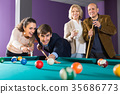Group of adults playing pool. 35686773